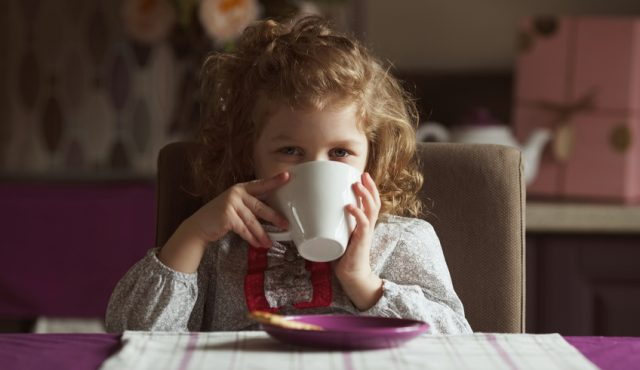 Little cute girl drinking from a white cup