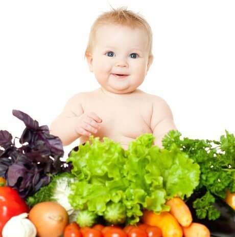 baby surrounded by vegetables