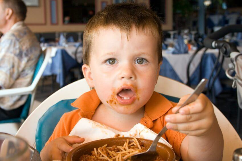 young boy eating spaghetti