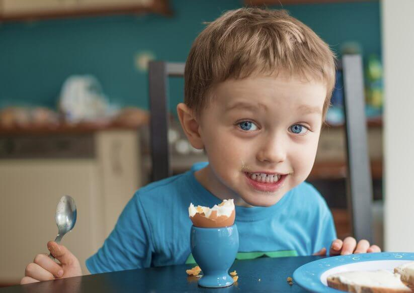 Small happy three year old boy eats an egg for breakfast