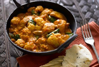 cauliflower and chicken curry in a bowl with bread