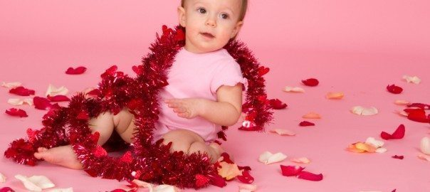Baby in pink, on pink background, sitting among rose petals