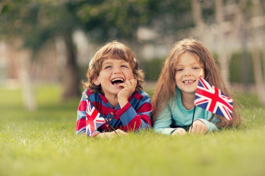 two british kids waving union jack flags