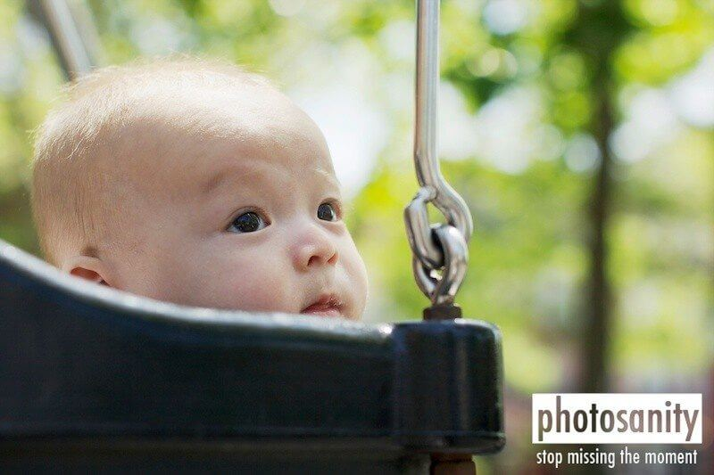 a baby sitting in a swing
