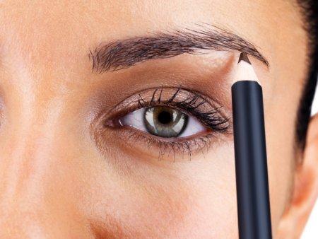 a woman applying eye liner