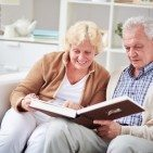 Elderly couple looking through family photo album