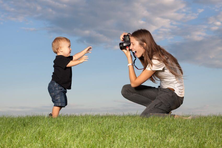 a mom taking a photograph of her son