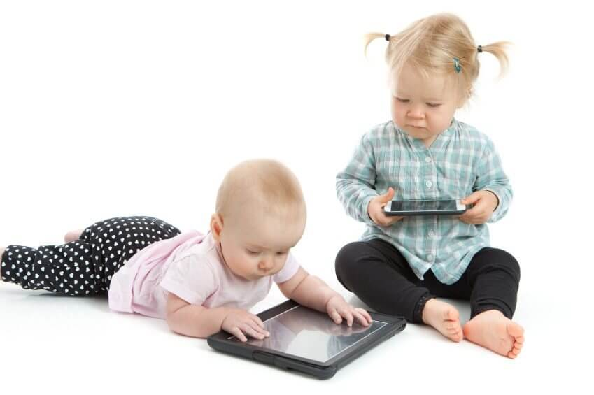 two toddlers playing with a smartphone and tablet
