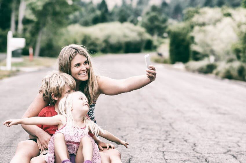 mom taking a selfie with her and her two kids