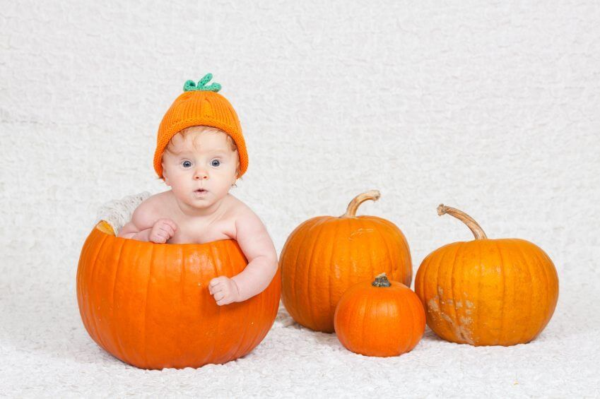 baby sitting inside a pumpkin