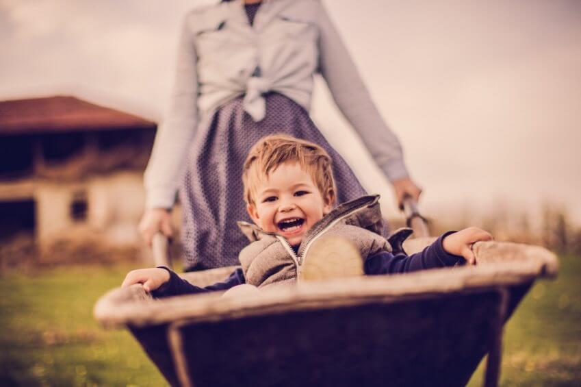 a boy taking a ride in a wheelbarrow