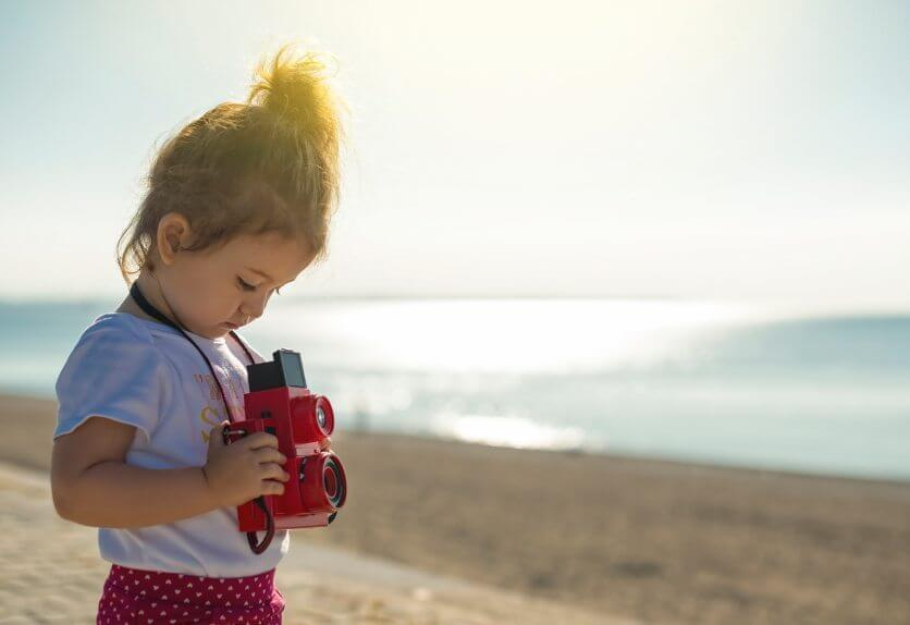 Cute little toddler taking pictures with a vintage camera
