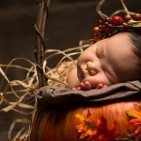 a baby sleeping on a pumpkin