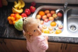 girl washing food in sink