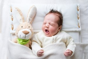 baby with bunny rabbit under blanket