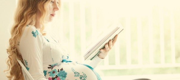 pregnant woman reading her tablet