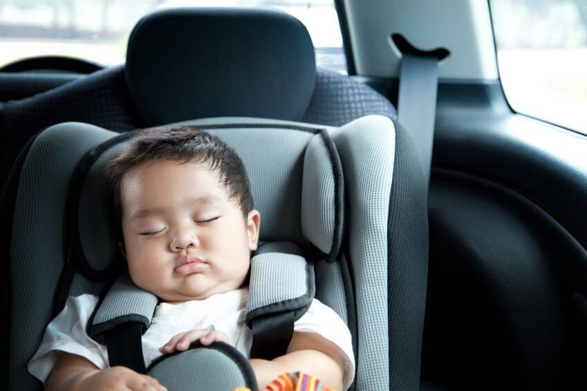 a baby asleep in a car seat