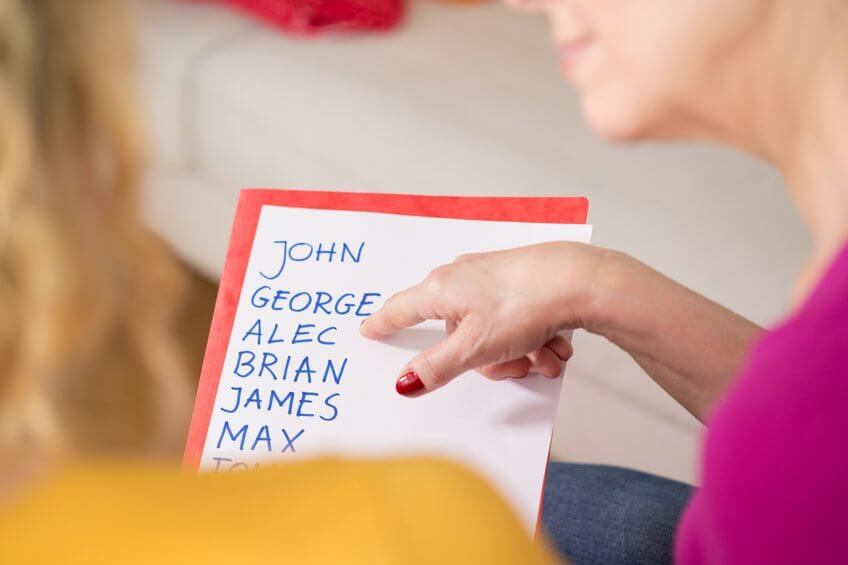 Close-up of pregnant woman holding the list of baby names