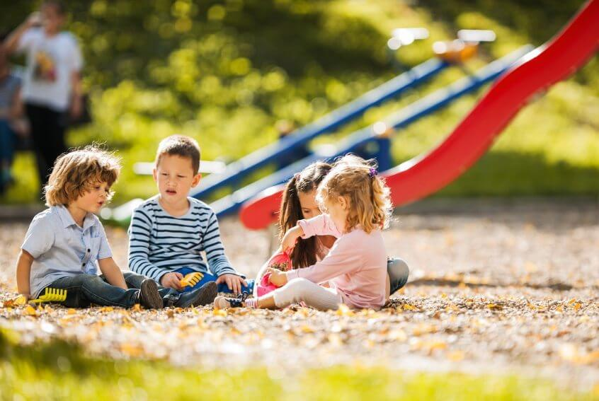 Four little children sitting together and playing on playground.