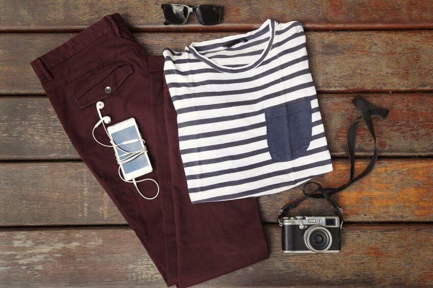 preppy clothes and camera on wooden dock