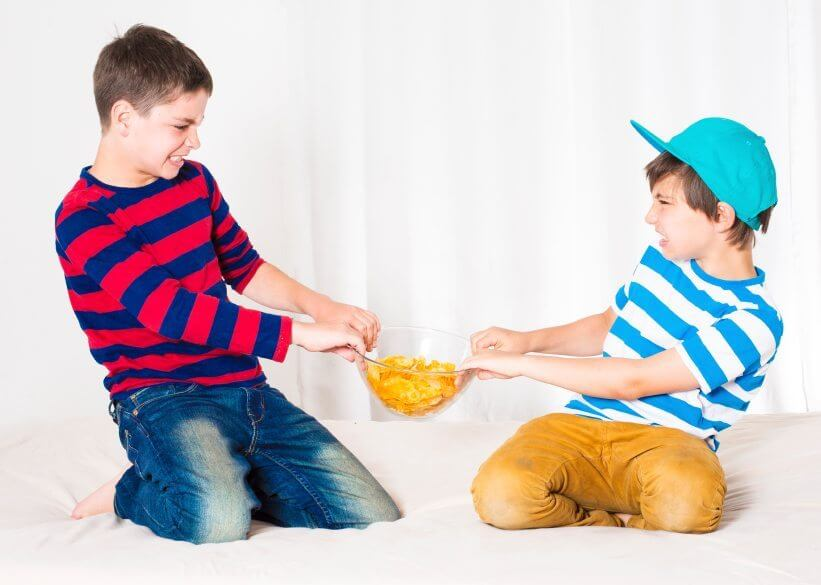 two young boys in bed and fighting over a bowl of potato chips