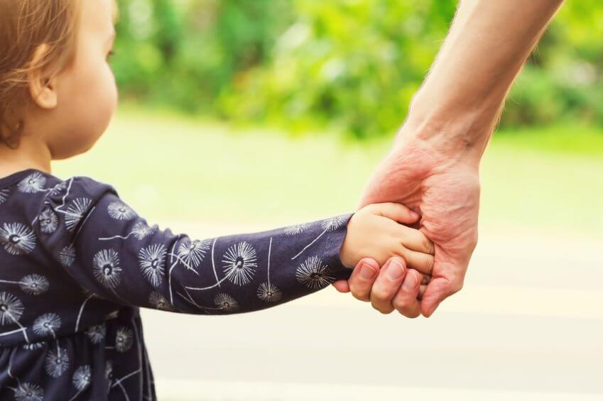 Toddler girl holding hands with her father outside