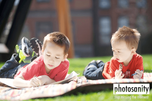 two kids coloring outside in the grass