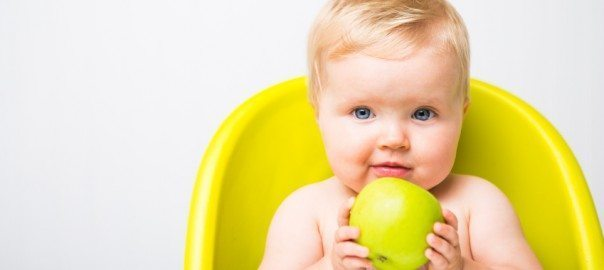 cute baby in a high chair holding an apple