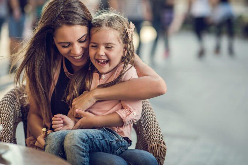 Cheerful mother spending a day in a cafe with her cute little daughter. They are laughing.