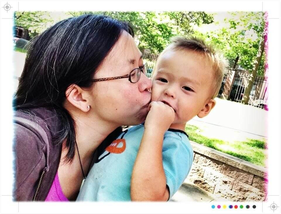 mom kissing son with outstretched arm