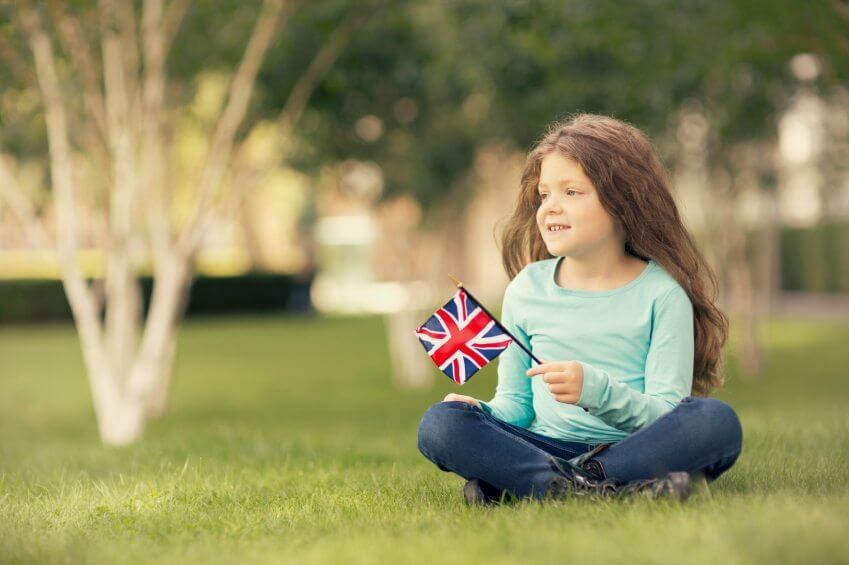 a girl waving a UK flag in a park