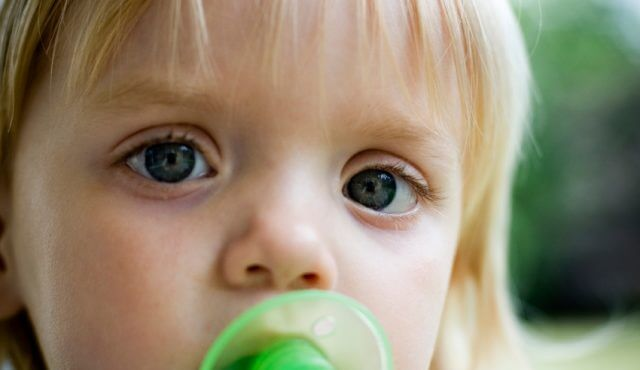 Slightly grainy image of a little girl with a pacifier with extreme narrow focus on her left eye