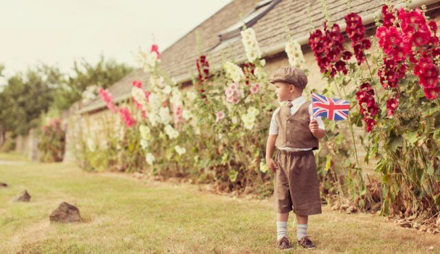 an english boy holding a uk flag outside in the garden