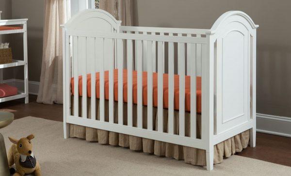 a white baby crib in a nursery