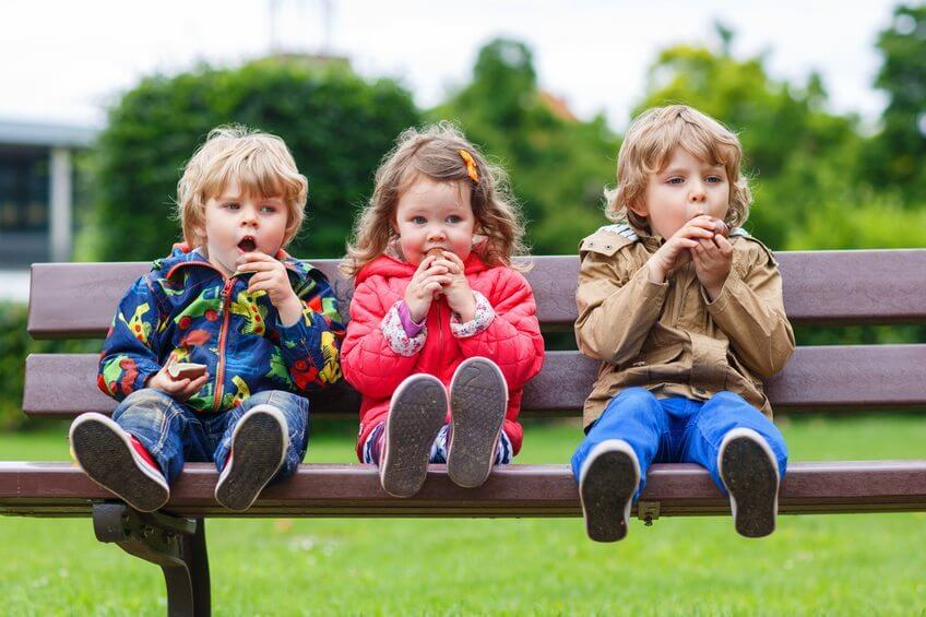 Two little boys and one girl eating chocolate