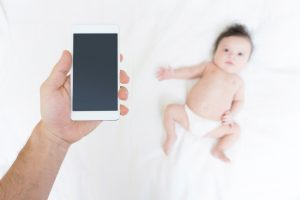 Smartphone and baby blurred at background