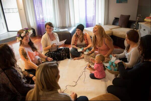 a group of women sitting in a circle at a baby shower