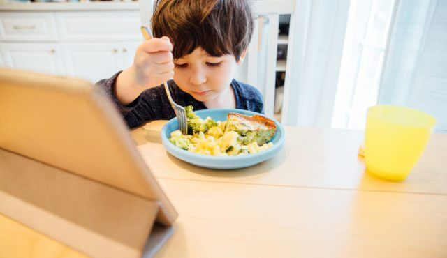 Little boy eats his meal while being entertained by a tablet computer