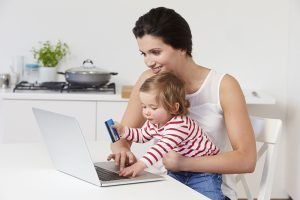 Mother With Child Using Laptop At Home Relaxing