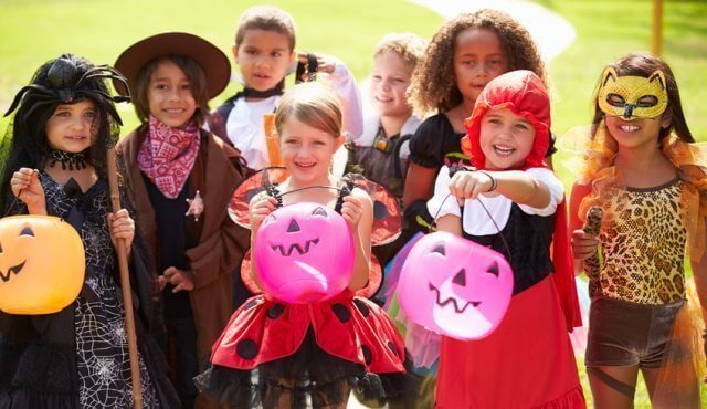 Children In Fancy Costume Dress Going Trick Or Treating Smiling To Camera