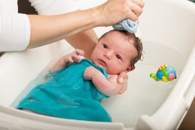 a mom washing her baby's face with a wash cloth