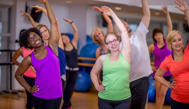 A multi-ethnic group of people are stretching after a fitness class in a gym studio.