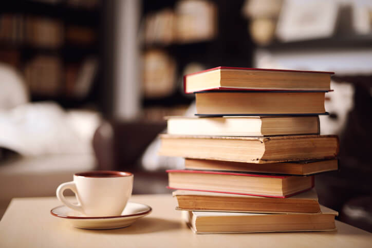 a pile of books with a cup of coffee sitting next to them