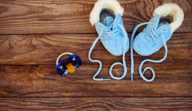 2016 year written laces of children's shoes and pacifier on the old wooden background. Toned image