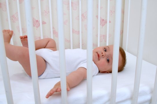 a baby lying on its back in a crib