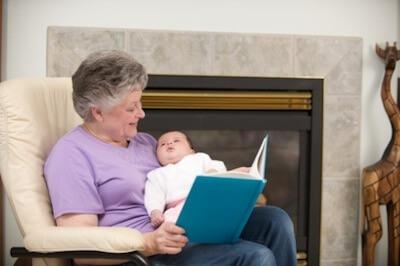 a grandma reading a book to her grandchild