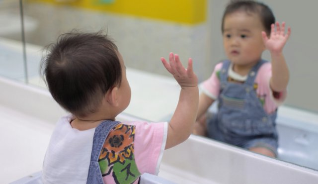 a baby waving hi to themselves in a mirror