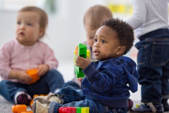 A multi-ethnic group of toddlers are sitting on the floor and are playing together with plastic blocks while on a play date.