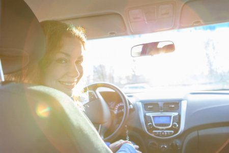 a mom smiling while the sun shines through the car screen
