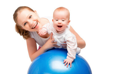 a mom playing with her baby on a gym ball